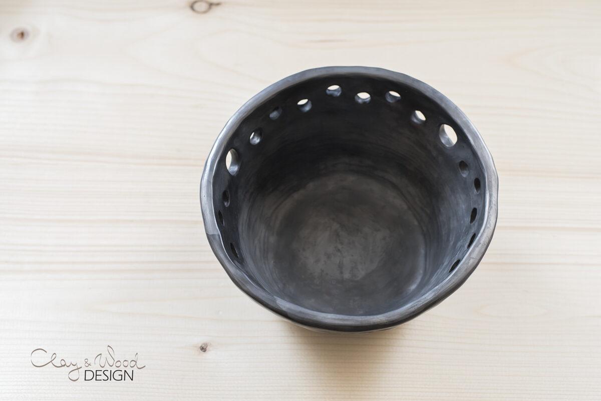 Melnās keramikas trauks ar dekoratīviem caurumiem