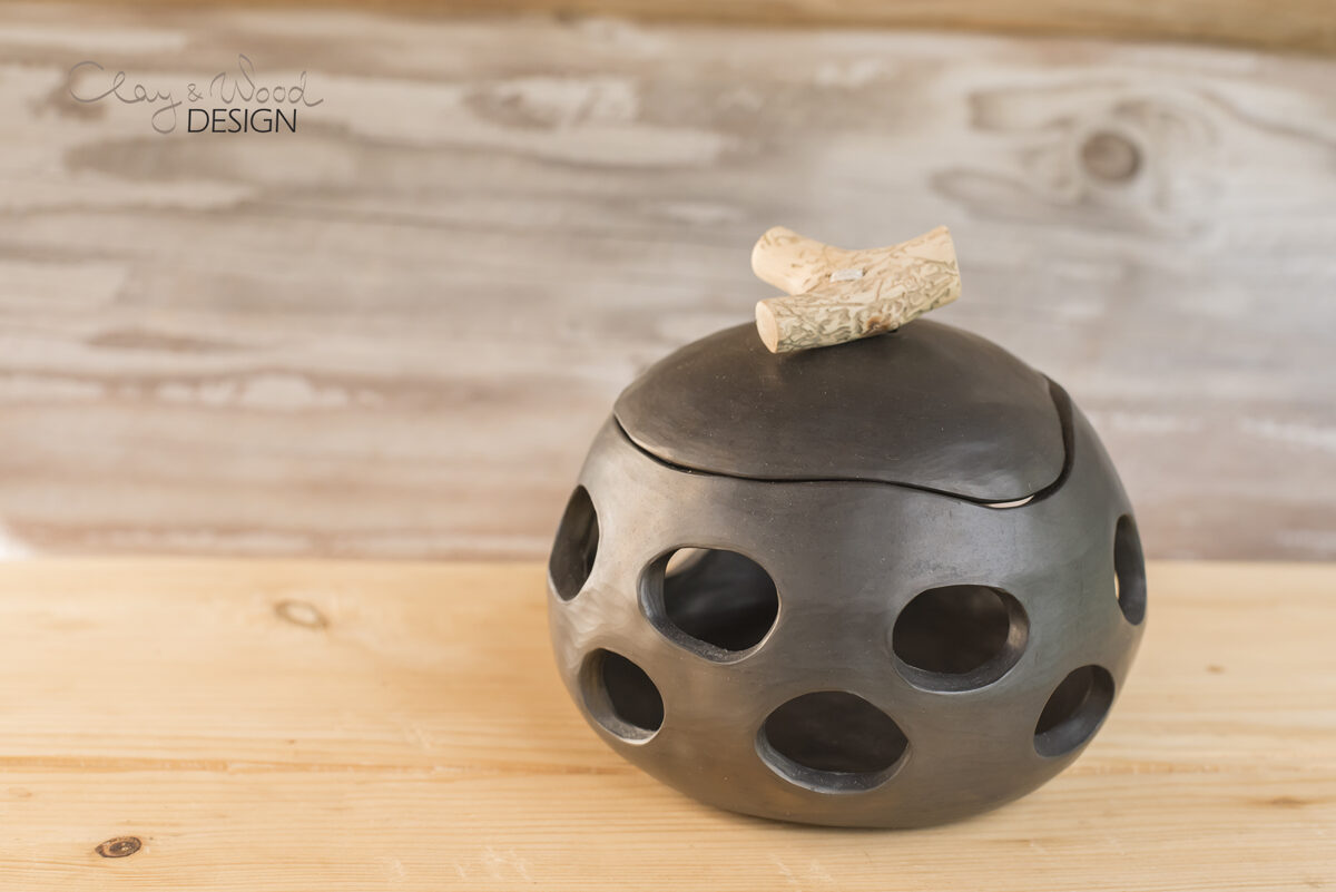 Melnās keramikas trauks ar caurumiem un vāciņu